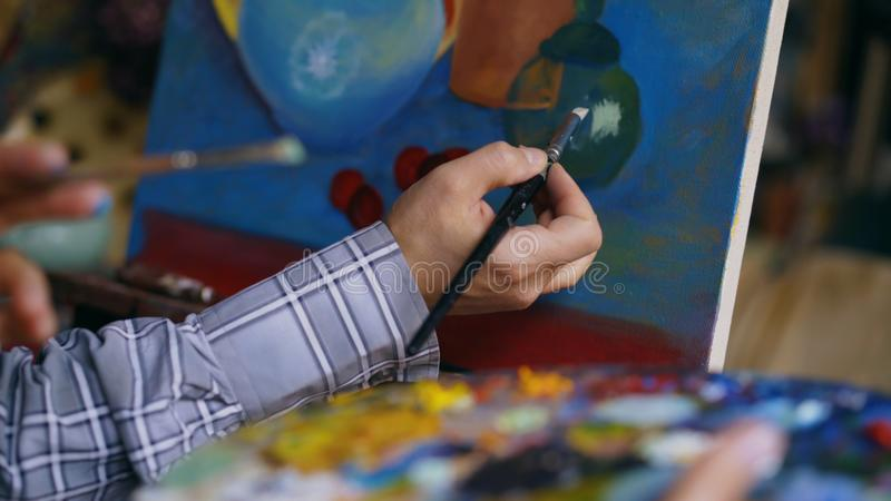 Slut upp av bilden för stilleben för målning för hand för man` s på kanfas i konst-skola arkivbild
