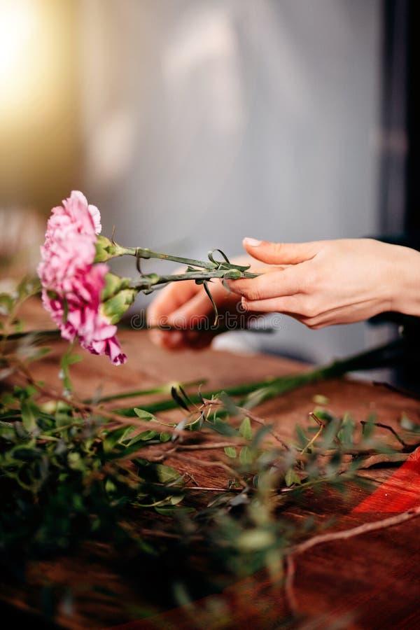 Slut upp av blomsterhandlaremannen som slår in blommor i papper på blomsterhandeln arkivbilder