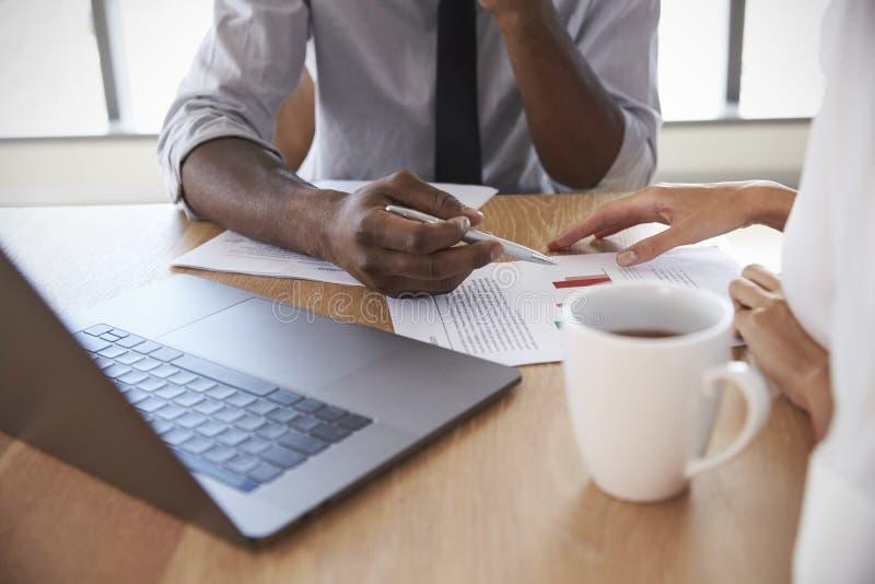 Slut upp av Businesspeople som arbetar på bärbara datorn i styrelse arkivfoto