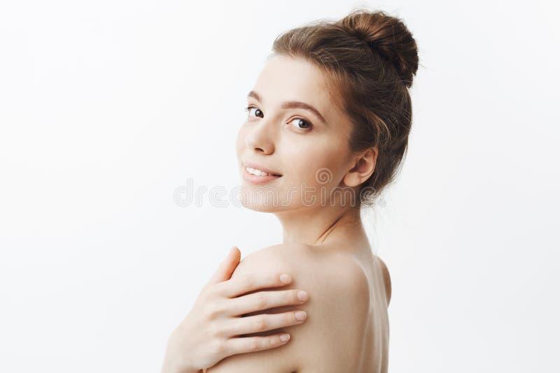 Slut upp av den charmiga unga attraktiva studentflickan med mörkt hår i bullefrisyren och den nakna kroppen som försiktigt ler royaltyfri bild