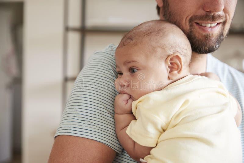 Slut upp av den faderComforting Newborn Baby sonen i barnkammare arkivbild