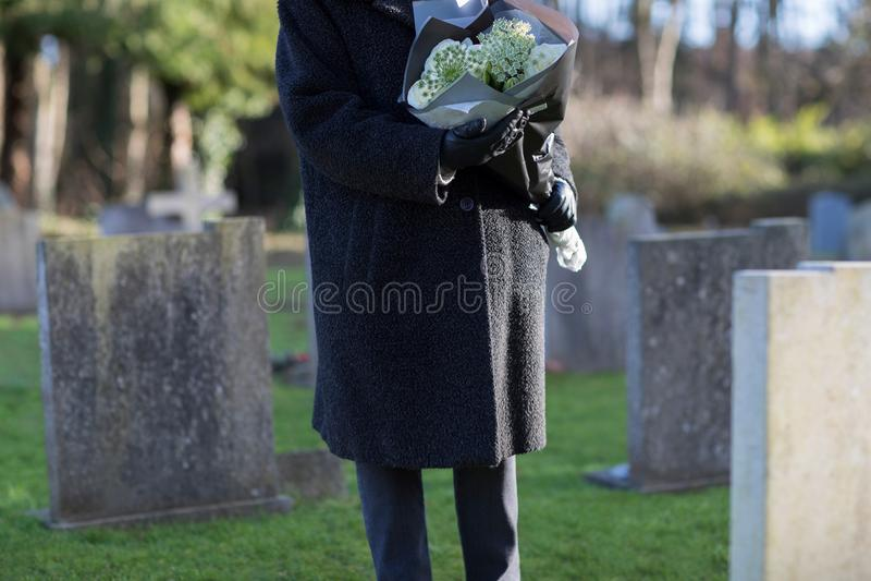 Slut upp av den höga kvinnan med blommor som står vid graven fotografering för bildbyråer