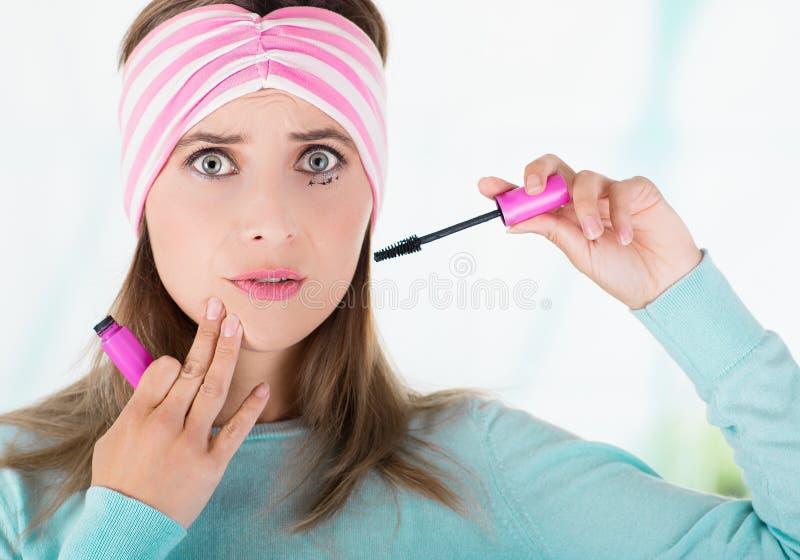 Slut upp av den imponerade unga härliga kvinnan som gör en röra genom att använda en ögonmascara i hennes öga, i en suddig bakgru royaltyfria bilder
