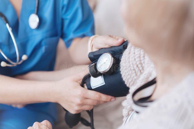Slut upp av den kvinnliga doktorn som övervakar arteriellt blodtryck royaltyfria foton