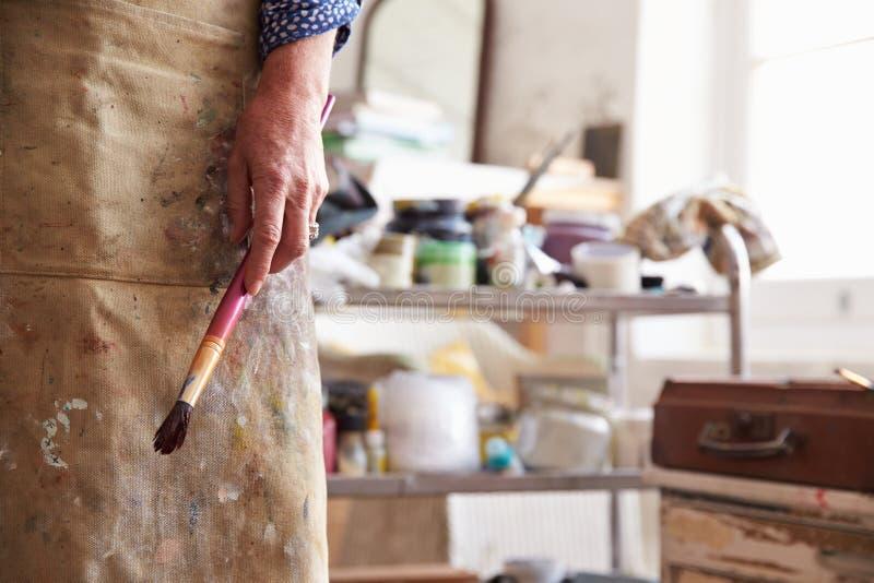 Slut upp av den kvinnliga konstnärHolding Brush In studion royaltyfri fotografi