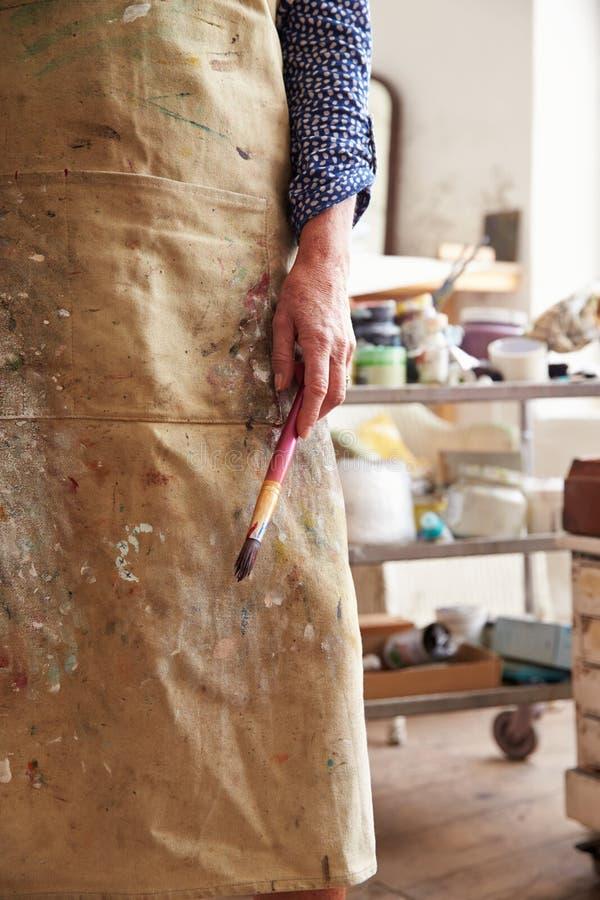 Slut upp av den kvinnliga konstnärHolding Brush In studion royaltyfri foto