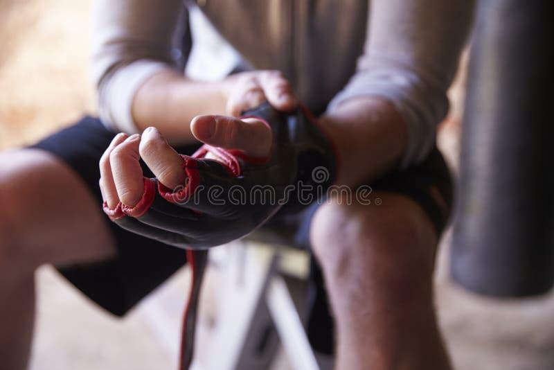 Slut upp av den manliga boxaren som sätter på handskar i idrottshall royaltyfri foto