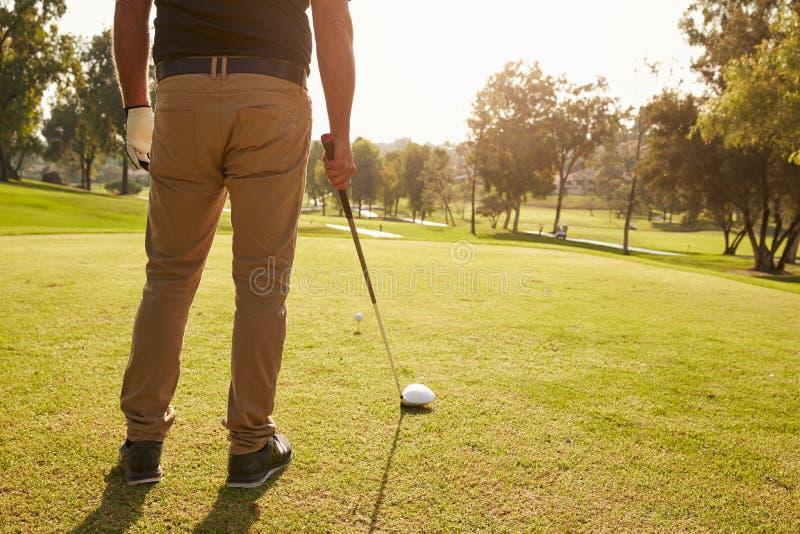 Slut upp av den manliga golfaren som ställer upp utslagsplatsen som skjutas på golfbana royaltyfri bild