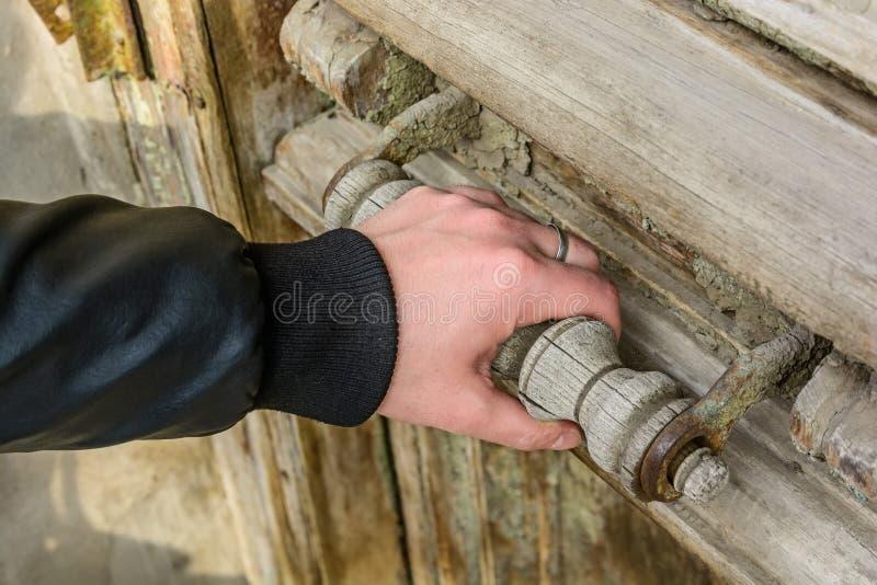 Slut upp av den manliga handen som öppnar den gamla trädörren royaltyfria foton