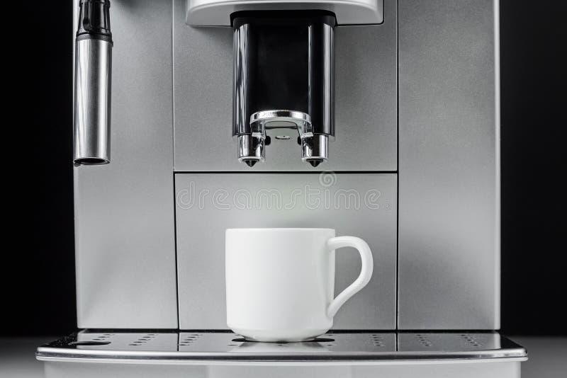 Slut upp av den moderna kaffemaskinen och vitkoppen på svart bakgrund fotografering för bildbyråer