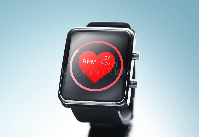 Slut upp av den smarta klockan för svart med symbolen för hjärtatakt royaltyfri foto