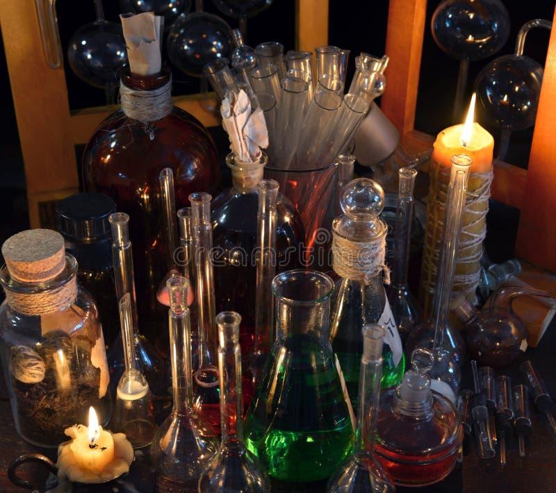 Slut upp av den tappningflaskor, flaskan och stearinljus i alkemilaboratorium arkivfoton