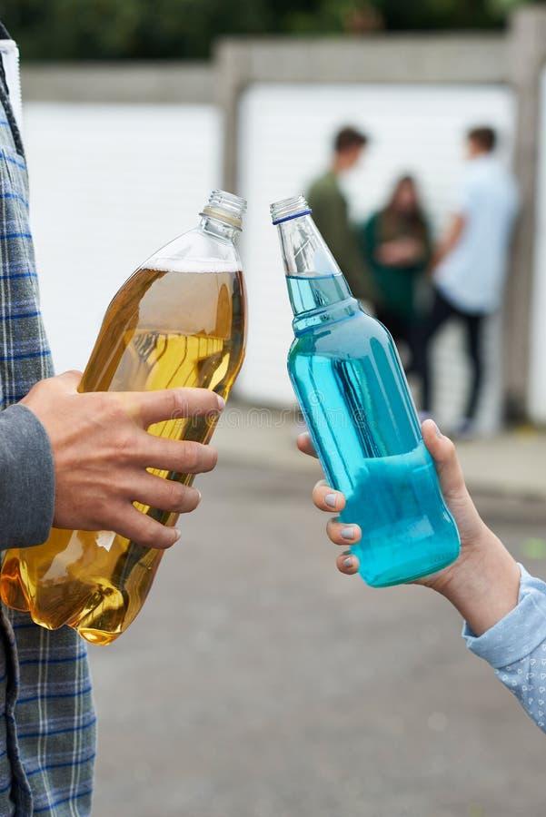 Slut upp av den tonårs- gruppen som dricker alkohol royaltyfri foto