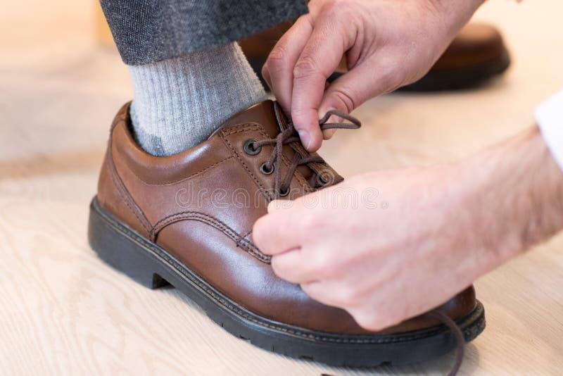 Slut upp av den vuxna sonen som hjälper den höga mannen att binda skosnöre royaltyfria foton