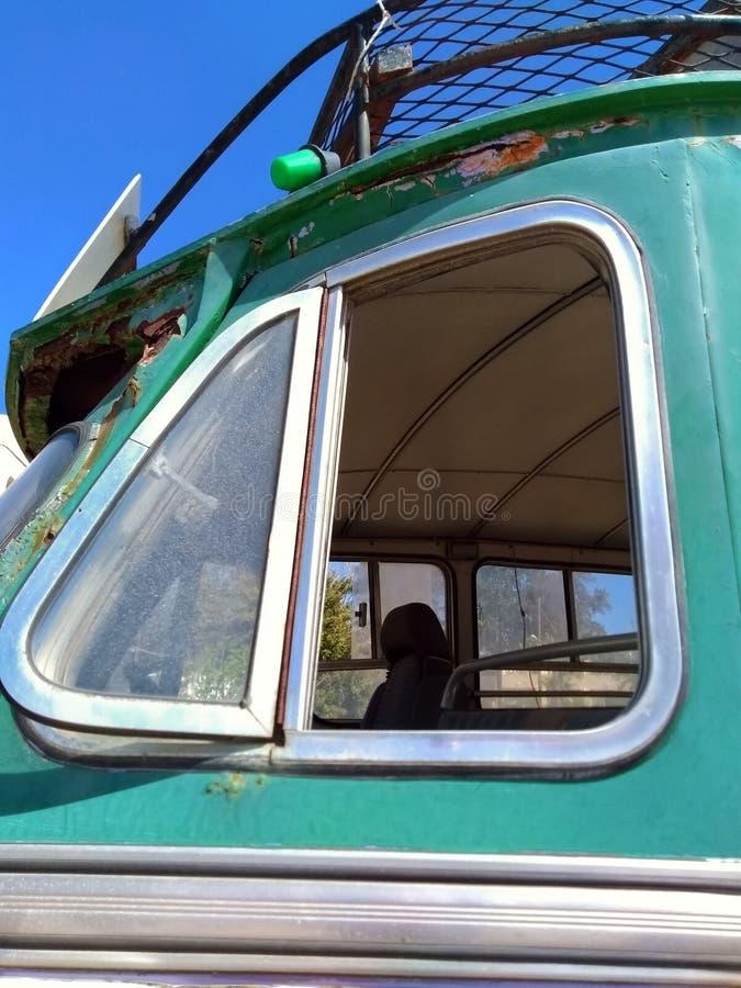 Slut upp av det öppna sidofönstret av en gammal grön rostig tappningbuss arkivfoto