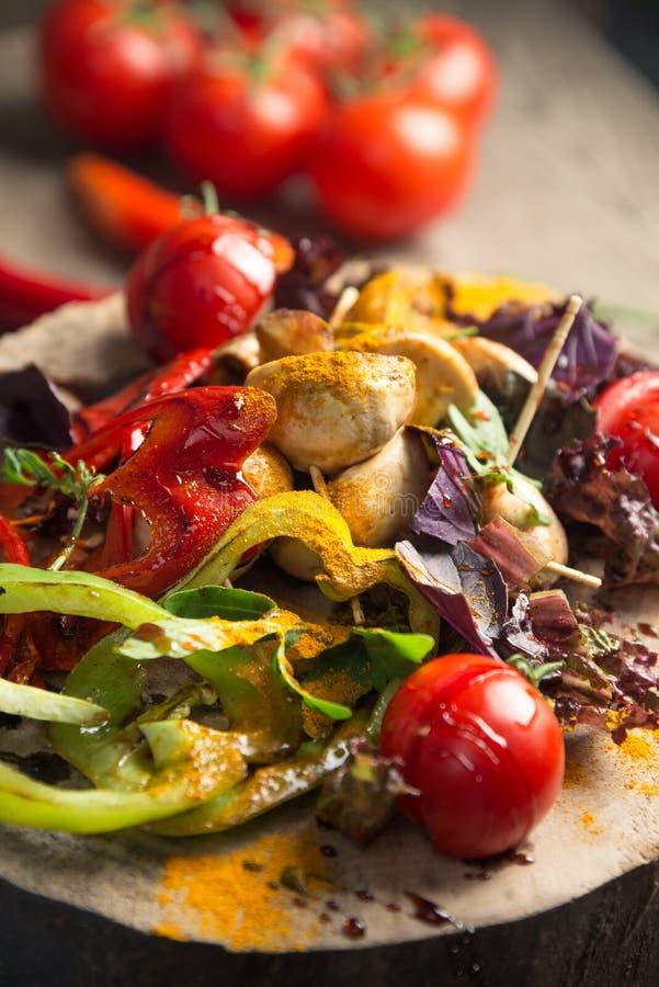 Slut upp av det färgrika grillade grönsakskottpengarmagasinet på träpannan och doppet som vilar på picknicktabellen arkivbild