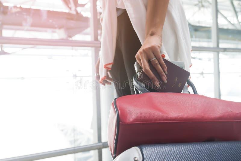 Slut upp av det hållande passet för kvinnahand och den släpande bagageresväskan royaltyfri foto