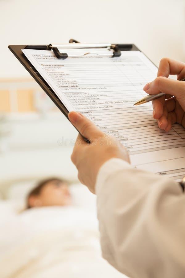 Slut upp av doktorshandstil på ett medicinskt diagram med tålmodign som ligger i en sjukhussäng i bakgrunden fotografering för bildbyråer
