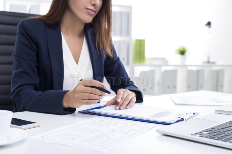 Slut upp av en brunbränd affärskvinna med en skrivplatta och en penna royaltyfri foto