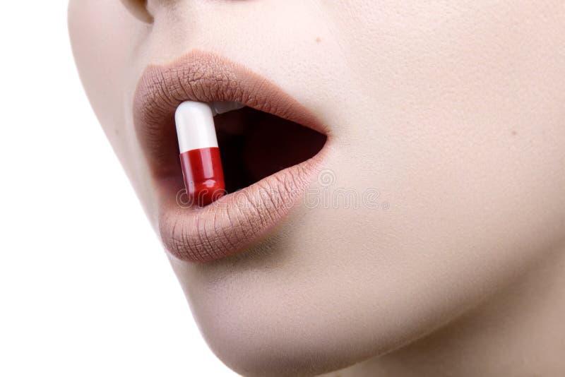 Slut upp av en framsida med den röda vita preventivpillermedicinen i hennes mun arkivbild