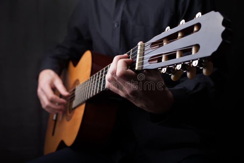 Slut upp av en gitarr som spelas fotografering för bildbyråer