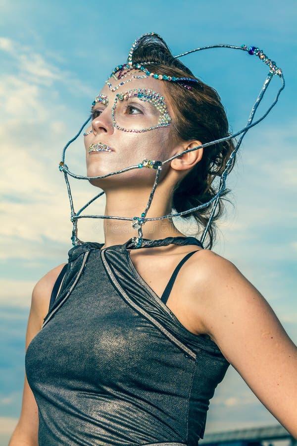 Slut upp av en härlig kvinna med kristaller som limmas på hennes framsida royaltyfri fotografi