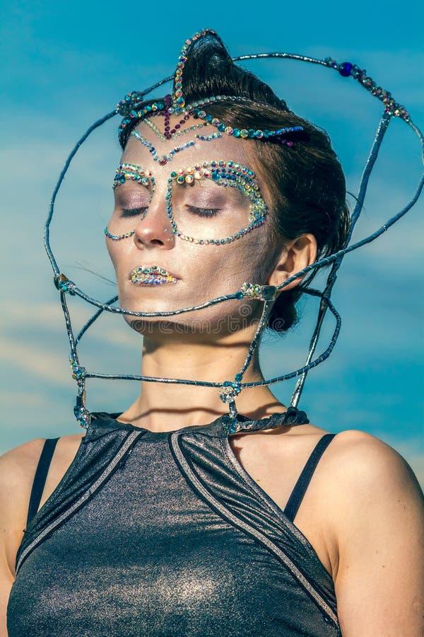 Slut upp av en härlig kvinna med kristaller som limmas på hennes framsida arkivfoto