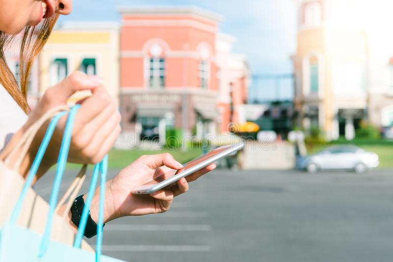 Slut upp av en håll för ung kvinna påsar för en shopping i henne hand och prata på hennes telefon, når att ha shoppat royaltyfria foton