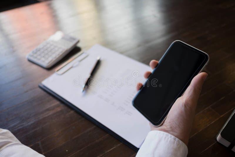 Slut upp av en man som anv?nder den smarta telefonen f?r mobil p? tabellen arkivbilder