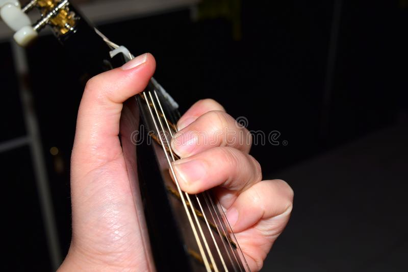 Slut upp av fingrar som spelar den klassiska gitarren Musiker som utför sånger royaltyfri bild