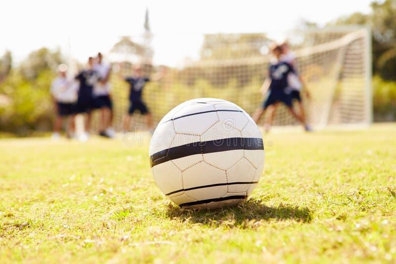 Slut upp av fotbollbollen med spelare i bakgrund royaltyfri foto