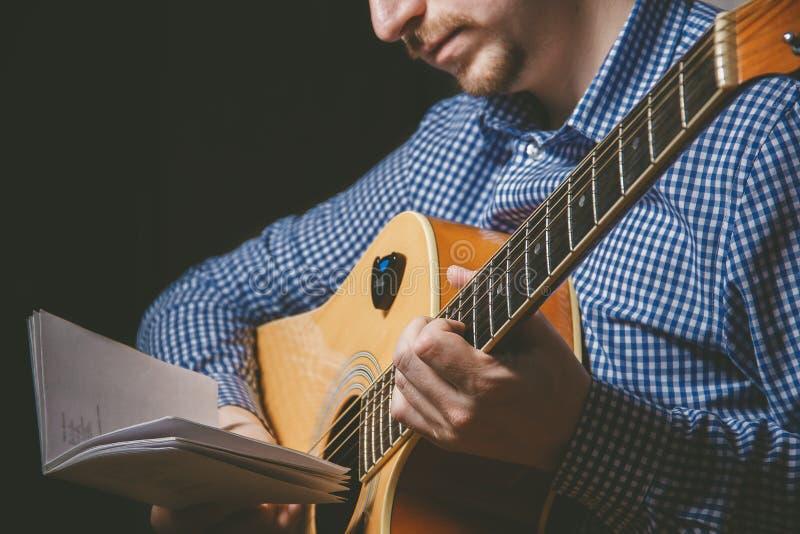 Slut upp av gitarristhanden som spelar gitarren royaltyfria bilder