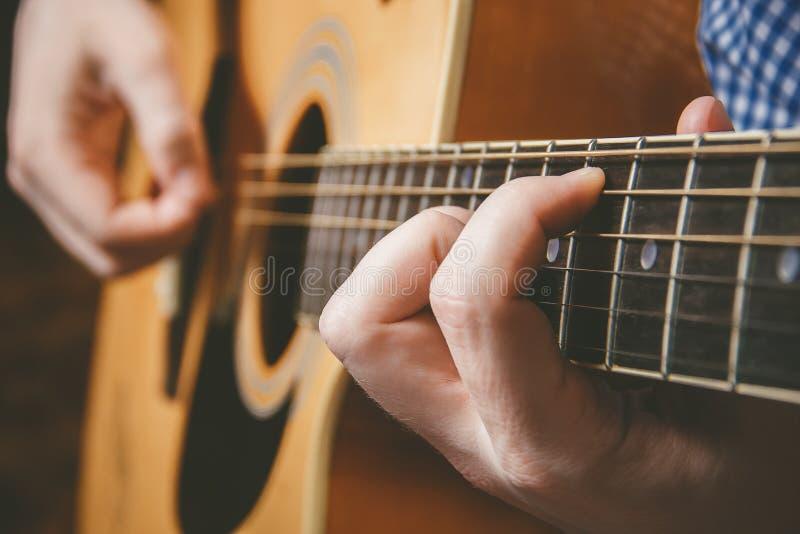 Slut upp av gitarristhanden som spelar gitarren arkivbilder