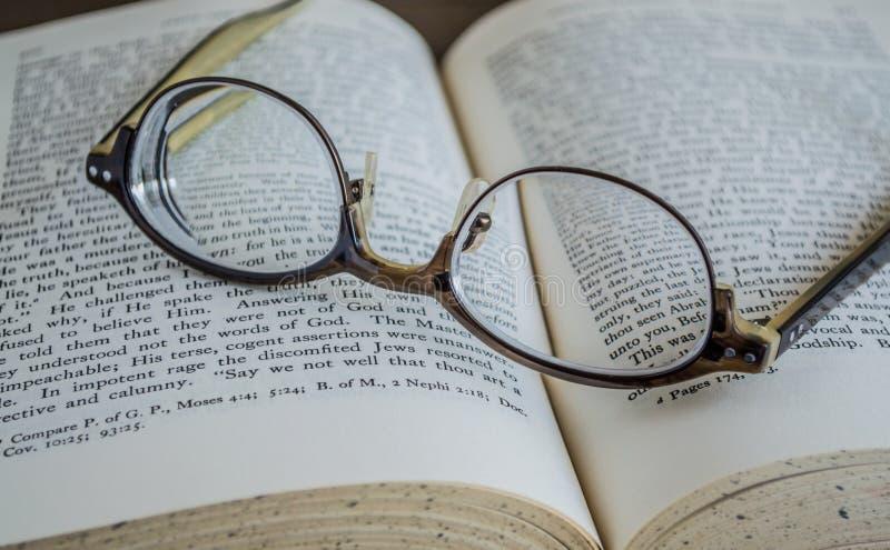 Slut upp av glasögon överst av en öppen bok arkivfoton