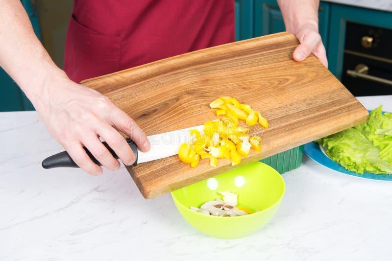 Slut upp av gul paprika i kuber Handen för man` s gör sallad med paprika och plocka svamp Slut upp av händer med kniven royaltyfri fotografi