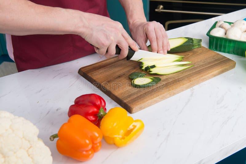 Slut upp av händer för man` som s klipper den gröna zucchinin Zucchini för snitt för händer för man` s med den vita kniven Slut u royaltyfria foton
