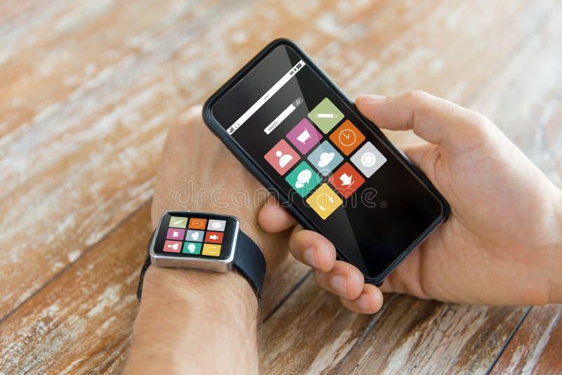 Slut upp av händer med den smarta telefonen och klockan arkivfoto