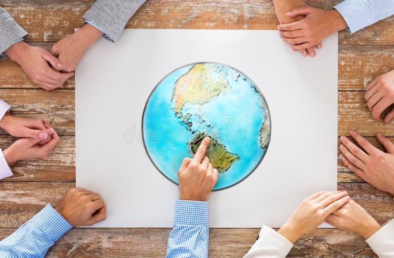Slut upp av händer med jordklotbilden på tabellen royaltyfri foto