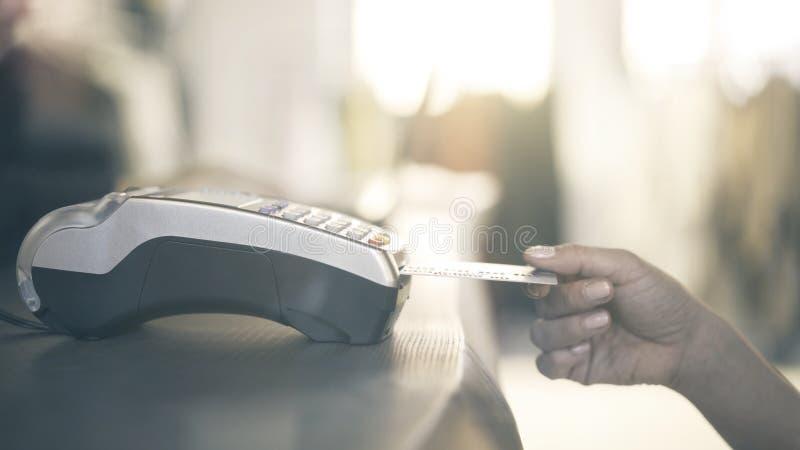 Slut upp av handen för kvinna som s betalar med en kreditkort genom att använda en bärbar maskin i lager Slut som skjutas upp royaltyfri bild
