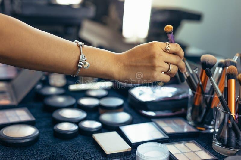 Slut upp av handen av makeupkonstnären som upp väljer en makeupborste fotografering för bildbyråer