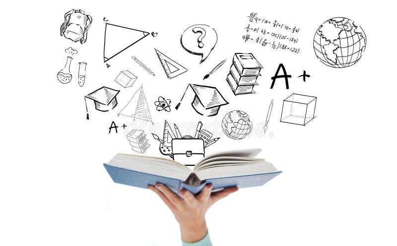Slut upp av handen med öppna bok- och skolaklotter royaltyfri illustrationer