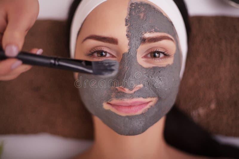 Slut upp av handen som applicerar den ansikts- maskeringen till kvinnaframsidan på skönhetsalongen royaltyfri bild