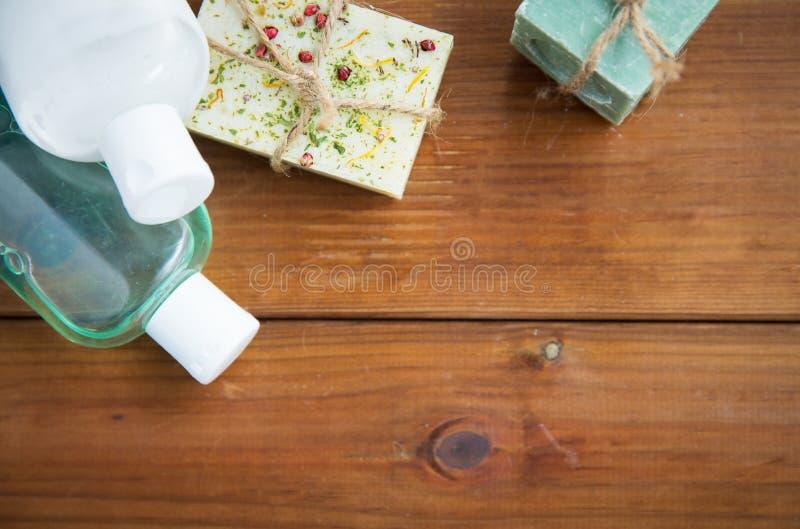 Slut upp av handgjorda tvålstänger och lotioner på trä arkivfoton