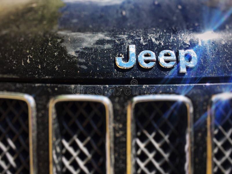 Slut upp av jeeplogoen på en smutsig Jeep Compass modell royaltyfri bild