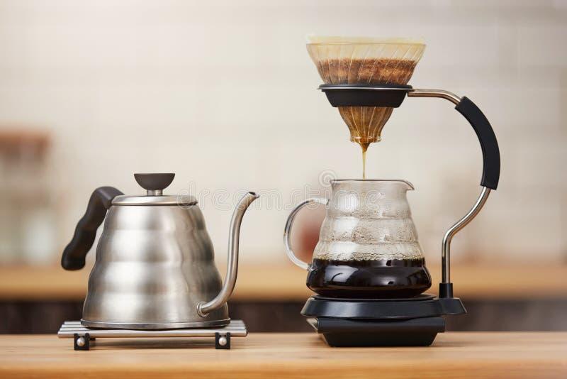 Slut upp av kaffe som bryggar grejer på trästångräknare royaltyfria foton