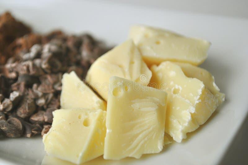 Slut upp av kakaosmör och rå ingredienser för framställning av choklad royaltyfri fotografi