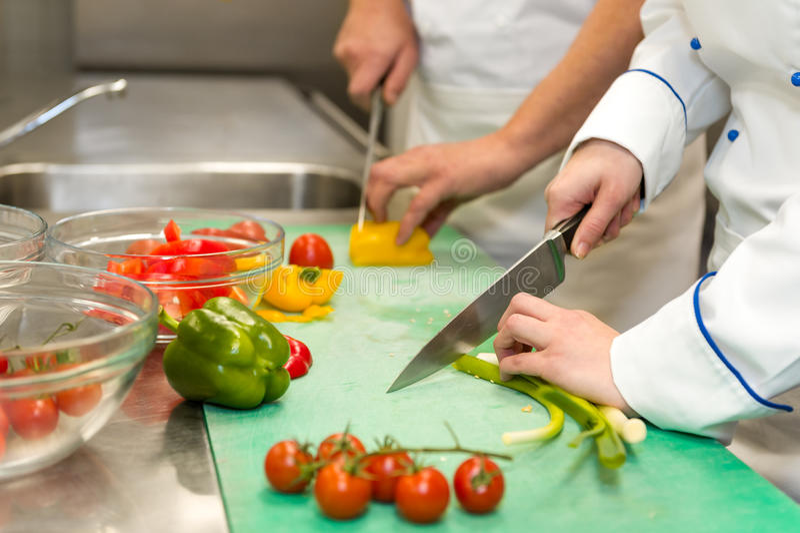 Slut upp av kockar som klipper grönsaker arkivfoton