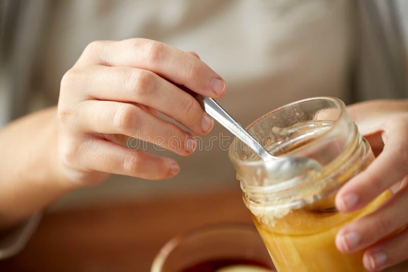 Slut upp av kvinnahänder med den honungkruset och skeden royaltyfri fotografi