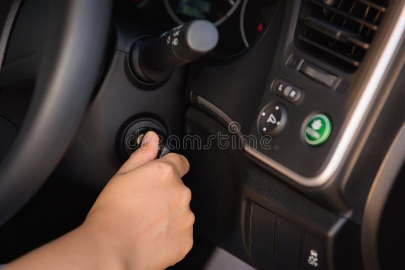 Slut upp av kvinnahanden som sätter in en tangent till den startande bilmotorn arkivfoton