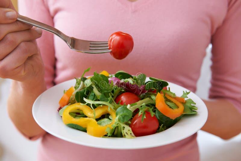 Slut upp av kvinnan som äter sund sallad royaltyfri foto